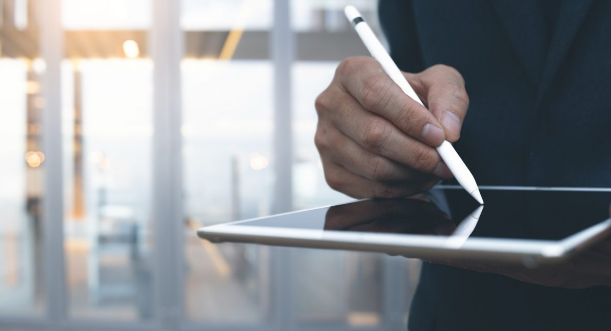 Closeup of  business man holding digital tablet on hand and using electronic pen while working at office. Pointing tablet screen with blurred background.
